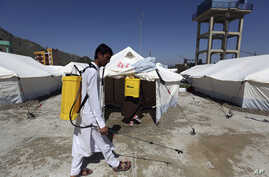 Afghan health workers in protective suits spray disinfectant on tents to help curb the spread of the coronavirus in the first quarantine camp for Afghan refugees crossing Torkham border from Pakistan to Afghanistan, April 4, 2020.