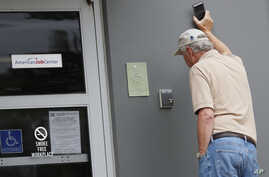 John Poe, a small business owner, speaks to an unseen state worker through an intercom speaker system