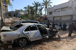 Libyans check the site of shelling on the residential area of souq al-Gomaa, north of the Libyan capital Tripoli, April 17, 2020.