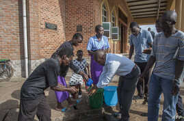 Parishoners wash hands as a preventive measure against the spred of the COVID-19 on the last day of full gatherings at the Saint Don Bosco Catholic Parish in Lilongwe, March 22, 2020.