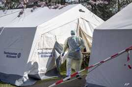 FILE - An employee of the Klinikum Bremen-Ost walks in protective clothing near, where coronavirus tests are being administered, in Bremen, Germany, March 16, 2020.