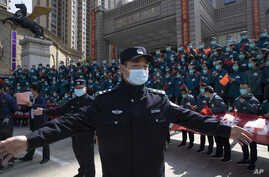 FILE - A policeman moves journalists back from an event held for the last group of medical workers who came from outside Wuhan to help the city during the coronavirus outbreak, in Wuhan, China, April 15, 2020.