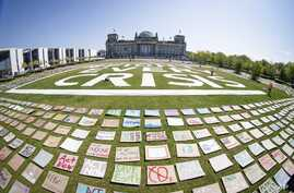 Activists of the Fridays for Future movement place protest posters for climate protection in front the German parliament building, the Reichstag, in Berlin, Germany, April 24, 2020.