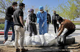 Men, some in protective gear, bury a coronavirus victim at a cemetery outside Tehran, Iran, March 30, 2020.