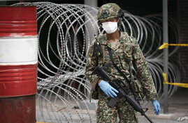 FILE - A solider stands guard in front of a barricaded building under lockdown, in downtown Kuala Lumpur, Malaysia, April 7, 2020.