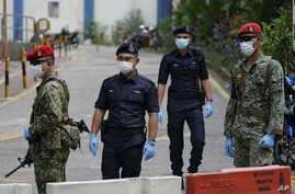 FILE - Military and police stand guard with protective face masks enforcing a coronavirus lockdown order, in Kuala Lumpur, Malaysia, March 31, 2020.