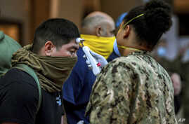 In this April 7, 2020, photo, released by the U.S. Navy, sailors assigned to the aircraft carrier USS Theodore Roosevelt, who have tested negative for COVID-19 and are asymptomatic, are checked at local hotels in Guam.