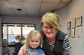 Alta, Iowa, hairstylist Joyce Rydstrom, shown in her salon with her granddaughter, says her emergency fund is shrinking while he