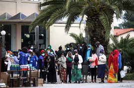 Migrants line up to receive sanitizers outside a hotel used as a refugee shelter, after authorities found several cases of the novel coronavirus and put the area under quarantine, in Kranidi, Greece, April 21, 2020.