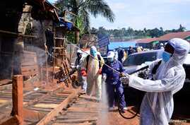Ugandan health officials wearing protective gear disinfect the Nakawa open-air market as part of the measures to prevent the spread of the coronavirus disease (COVID-19), in Nakawa division of Kampala, April 17, 2020.