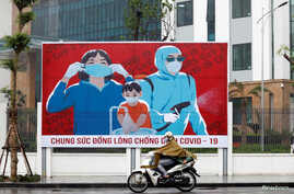 A man wears protective mask as he rides past a propaganda banner promoting prevention against the coronavirus disease (COVID-19) in Hanoi, Vietnam, April 3, 2020.