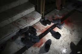 FILE - Blood stains and shoes remain on stairs inside a Sikh house of worship, in the aftermath of an attack on Sikh believers, in Kabul, Afghanistan, March 25, 2020.