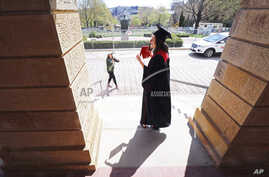 In this Thursday, May 7, 2020 photo University of Wisconsin-Madison 2020 graduate Sara Krueger poses for photographs with her…