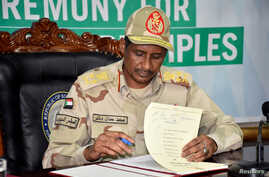 General Hamdan Dagalo, a member of the sovereign council and head of the paramilitary Rapid Support Forces (RSF), signs the…