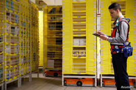 FILE - An employee works next to drive units robots at the Amazon fulfilment center in Bretigny-sur-Orge near Paris, France, October 22, 2019.