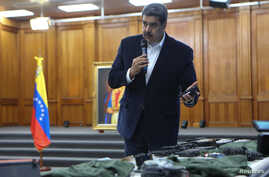 Venezuela's President Nicolas Maduro shows military equipment during a meeting with the Bolivarian armed forces at Miraflores…