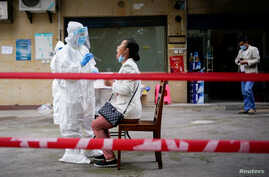 A medical worker in protective suit conducts nucleic acid testings for residents at a residential compound in Wuhan, the…