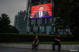 A screen at a department store shows Chinese President Xi Jinping during the opening session of the CPPCC