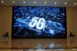 A 5G logo is displayed on a screen outside the showroom at Huawei campus in Shenzhen city, China