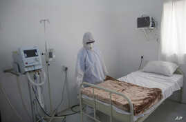 A medical staff member works on setting up an isolation room at a coronavirus quarantine ward at a hospital in Sanaa, Yemen,…