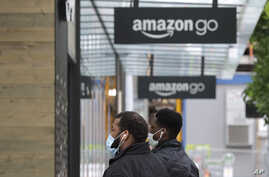 Two people wearing masks walk near an Amazon Go store, Thursday, April 30, 2020, in downtown Seattle. Amazon.com is expected to…