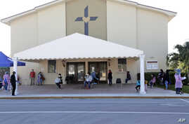 People practice social distancing as they wait at a COVID-19 testing site at Sacred Heart Church, May 5, 2020, in Fla.