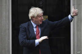 "Britain's Prime Minister Boris Johnson joins in the applause on the doorstep of 10 Downing Street in London during the weekly ""Clap for our Carers"" Thursday, May 7, 2020."