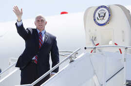 Vice President Mike Pence waves as he stops off Air Force Two after arriving at the Des Moines International Airport before…