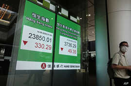 A man wearing face mask walks past a bank electronic board showing the Hong Kong share index at Hong Kong Stock Exchange…