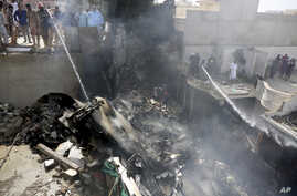 Fire brigade staff try to put out fire caused by plane crash in Karachi, Pakistan, May 22, 2020.