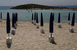 FILE - Rows of closed sun umbrellas are seen on a nearly empty beach in Cyprus' seaside resort of Ayia Napa, a favorite among European and other tourists, May 13, 2020