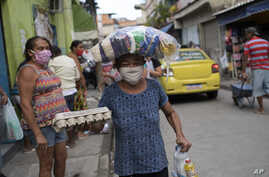 """A woman wearing a protective face mask carries food donated by """"Eu sou Eu"""" or """"I am me,"""" a non-profit run by former inmates, during the coronavirus pandemic, at the Para-Pedro favela in Rio de Janeiro, Brazil, May 8, 2020."""