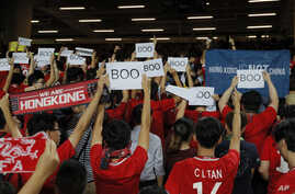 """FILE - Hong Kong soccer fans turn their backs and boo the Chinese national anthem as they chant """"Hong Kong is not China"""" during a World Cup qualifying soccer match between Hong Kong and Iran, in Hong Kong, Sept. 10, 2019."""
