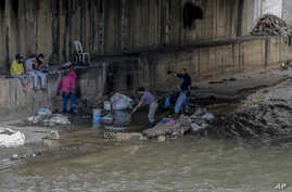 Men sift through a sewer for valuables along the foreshore of the Abou Ali River, in the northern city of Tripoli, Lebanon, May 5, 2020.