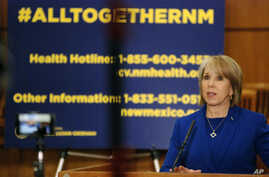 New Mexico Gov. Michelle Lujan Grisham confirms a new coronavirus infection that has no apparent link to travel, March 18, 2020, during a news conference on the floor of the state House of Representatives in Santa Fe, N.M.