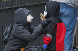 FILE - A woman adjusts her child's protective mask as they wait in line to be screened for COVID-19 at Gotham Health East New York, April 23, 2020, in the Brooklyn borough of New York City.