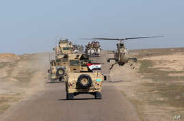 FILE - A convoy of Iraqi forces is seen moving through the Samarra desert, on the border between Anbar and Salahuddin provinces, Iraq, March 9, 2016.