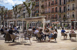 Customers sit and drink on a terrace bar in Tarragona, Spain, May 11, 2020.