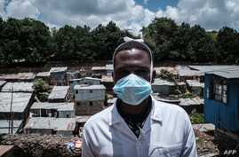 A staff member of local NGO Shining Hope for Communities (SHOFCO) pose for a portrait while wearing a face mask as a preventive…