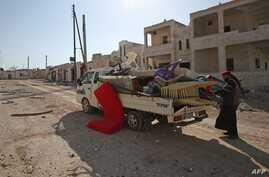 A man loads his belongings into a truck as he prepares to flee the village of al-Nayrab, about 14 kilometres southeast of the…