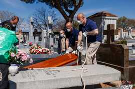 TOPSHOT - Mortuary employees wearing face masks burry the coffin of a COVID-19 coronavirus victim at Fuencarral cemetery in…