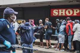 TOPSHOT - A South African policeman points his pump rifle to disperse a crowd of shoppers in Yeoville, Johannesburg, on March…