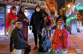 Iranians wearing maks against the coronavirus Covid-19 gather outside their buildings after an earthquake was felt in the…