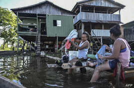 Women wash clothes at the Amazon river in Leticia, Colombia on May 13, 2020, amid the new coronavirus pandemic. - Colombia will…
