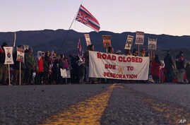FILE - In this July 15, 2019 file photo, demonstrators block a road at the base of Hawaii's tallest mountain, in Mauna Kea,…