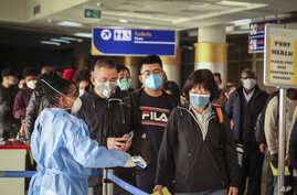 Passengers arriving on a China Southern Airlines flight from Changsha in China are screened for the new type of coronavirus,…