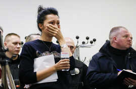 A Ukrainian International Airline company worker reacts during a briefing at Borispil international airport outside Kyiv,…