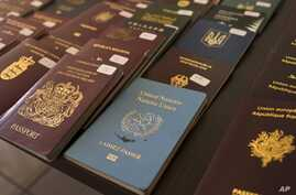 In this Wednesday, Feb. 28, 2018 photo Greek authorities present confiscated passports and identification cards at the Athens…