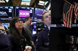Specialist Erica Fredrickson works with a colleague on the floor of the New York Stock Exchange, Monday, Feb. 24, 2020. Stocks…