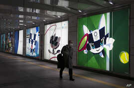A man with a mask walks past large displays promoting the Tokyo 2020 Olympics Monday, Feb. 24, 2020, in Tokyo. (AP Photo/Jae C…
